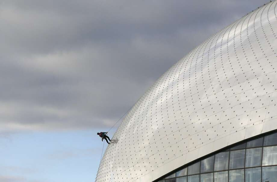 A worker rappels down the roof of the Bolshoy Ice Dome, site of the ice hockey competitions at 2014 Winter 