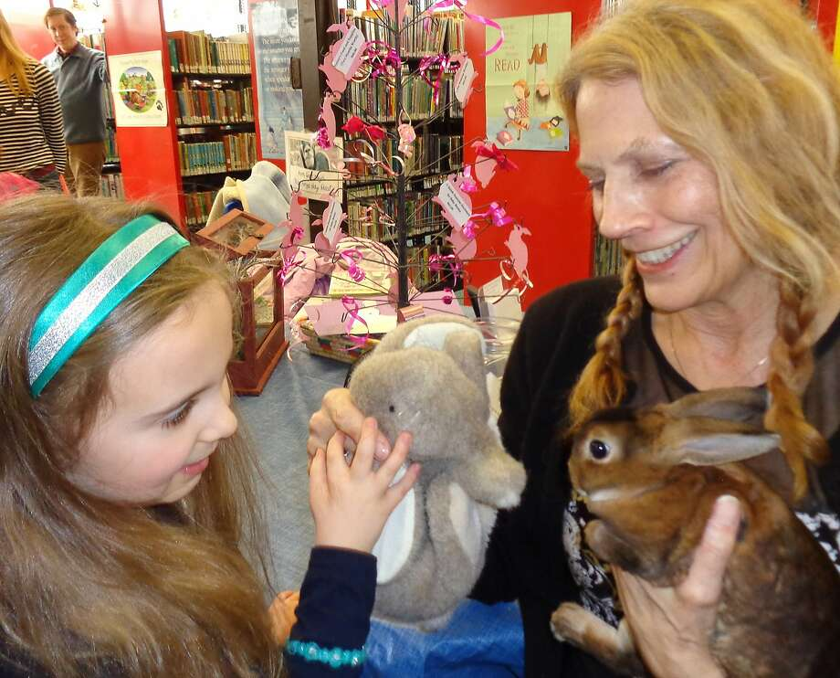 See what happens to bunnies who don't behave:The new rabbit of the Pequot Library in Fairfield, Conn.,   meets 7-year-old Allison Cancro's stuffed rabbit. Helping with the introductions is librarian Susan Ei. Photo: Meg Barone, Connecticut Post