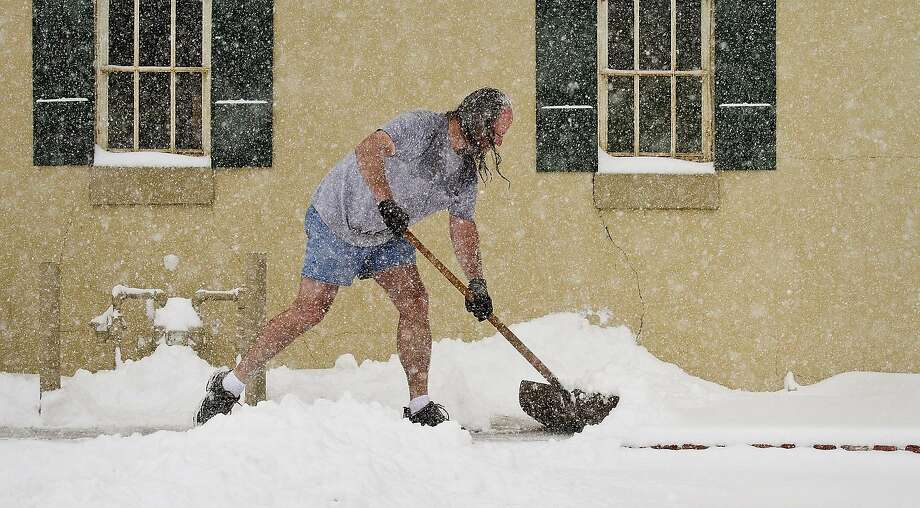 A little frostbite never hurt anyone:Troy Welty, who doesn't let weather conditions dictate his wardrobe selection, shovels snow in front of Mathew's Gallery in Wichita, Kan. Photo: Mike Hutmacher, Associated Press