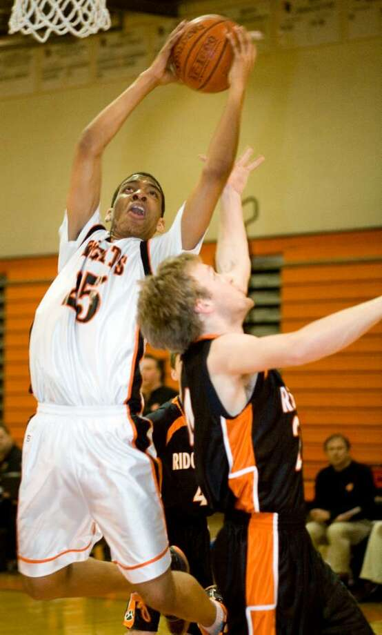 Stamford High School's #25 Terrance Dimitri, left, takes a shot on basket as he's defended by Ridgefield High School's #24 Ryan Curnal during a boys basketball game in Stamford on Feb. 5, 2010. Photo: Kerry Sherck / Stamford Advocate Freelance