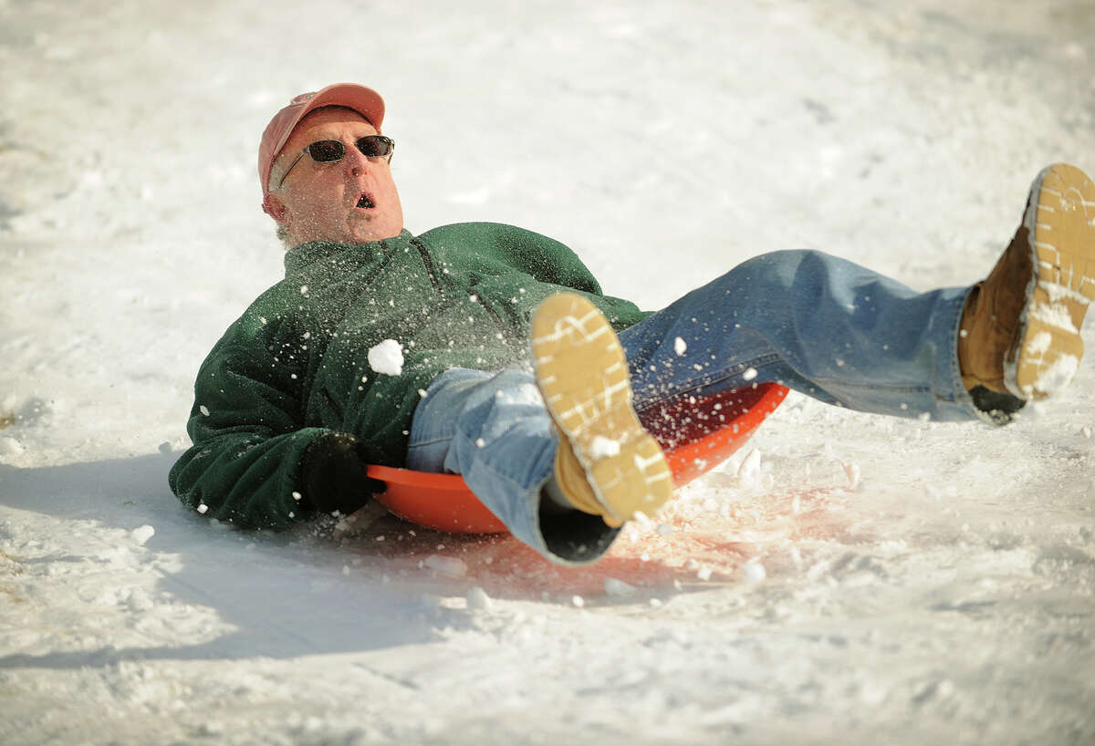 Kees Adema, of Fairfield, goes for a harrowing run down the sled hill during an afternoon of sledding with his grandchildren at Sturges Park in Fairfield on Tuesday, February 4, 2014.