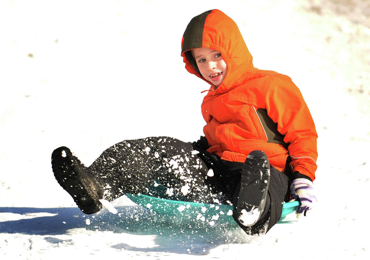 Julian Daou, 7, of Woodbury, goes for a ride on the sled hill at Sturges Park in Fairfield on Tuesday, February 4, 2014.
