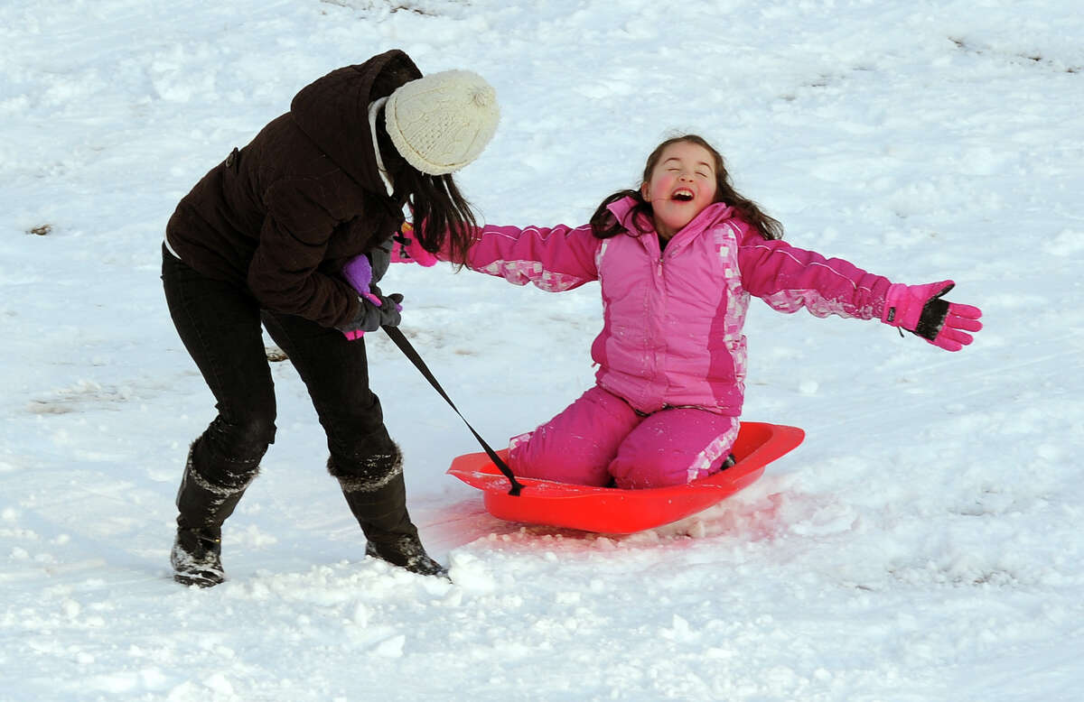 Julia Allen, 8, of Stratford, sings as her mom Bea pulls her in her sled at Boothe Memorial Park in Stratford, Conn. on Monday, February 4, 2014.