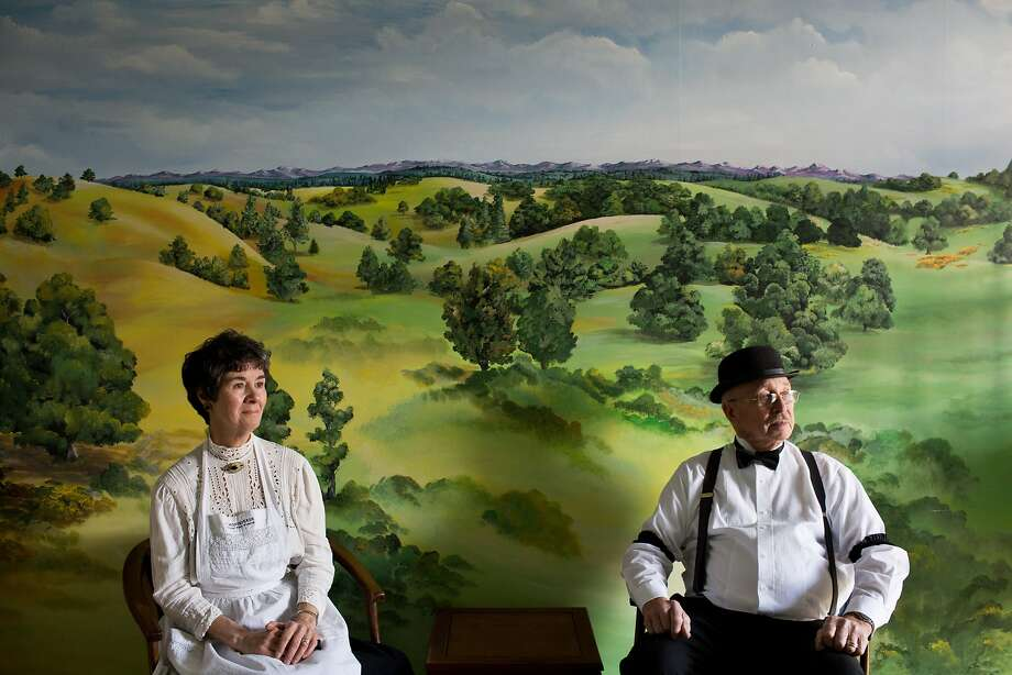 Volunteer docents Faye and Bob Fyock sit in front of a mural in the J. Monteverde General Store Museum. The store opened in 1898. Photo: Jason Henry, Special To The Chronicle