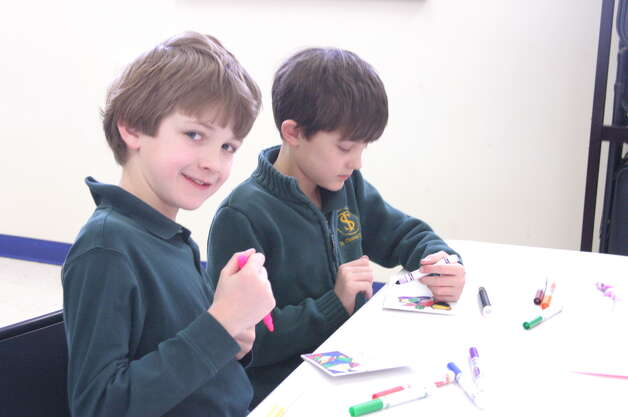 St. Thomas the Apostle Elementary School second-graders David Lichtenwalner, left, and Jasper Atkinson were among those who fanned out across the region to volunteer on Tuesday Jan. 28 as a service component to Catholic Schools Week. Third through eight graders spent the day spreading warmth at Catholic Charities' sites by preparing meals, filling donation boxes, making valentines for clients, and visiting with seniors.  (Submitted by Paul McAvoy)