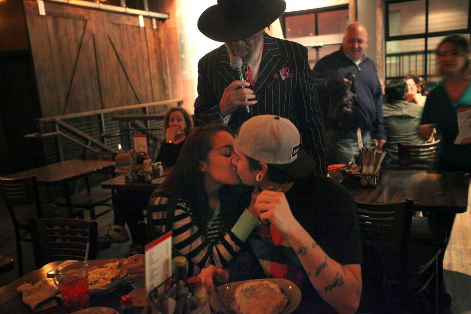 Blues singer Willie G. encourages couples like Erika Hernandez and Jacob Melendrez to kiss at Lou's Fish Shack. Photo: Leah Millis, The Chronicle