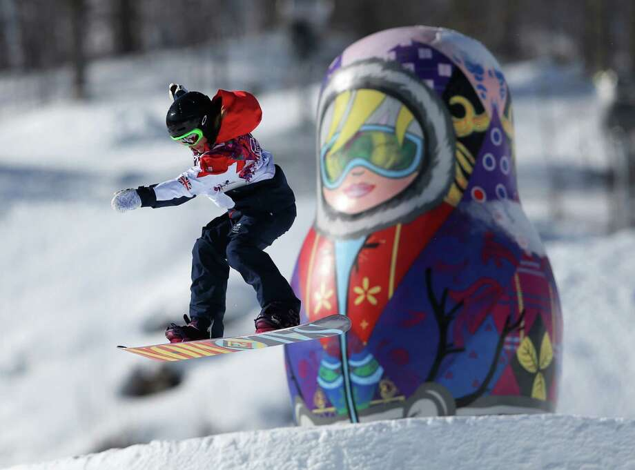 A competitor takes a jump past a giant matryoshka doll during a snowboard slopestyle training session at the Rosa Khutor Extreme Park, prior to the 2014 Winter Olympics, Tuesday, Feb. 4, 2014, in Krasnaya Polyana, Russia. (AP Photo/Sergei Grits) Photo: Sergei Grits, Associated Press / AP