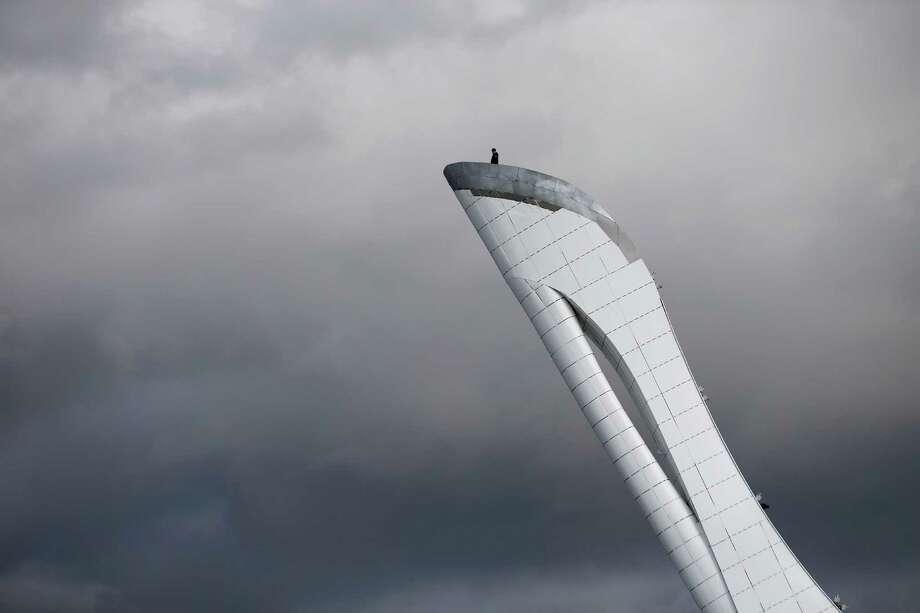 A worker is dwarfed against the sky as he stands at the top of the Olympic cauldron ahead of the 2014 Winter Olympics, Tuesday, Feb. 4, 2014, in Sochi, Russia. (AP Photo/Wong Maye-E) Photo: Wong Maye-E, Associated Press / AP