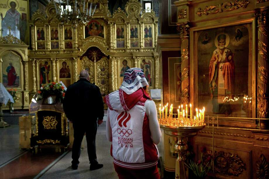 A Russian woman wearing a jacket of the Russian Olympic team prays inside St. Michael the Archangel Cathedral, Tuesday, Feb. 4, 2014, in Sochi, Russia. The opening ceremony for the games will be held on Feb. 7.   (AP Photo/Bernat Armangue) Photo: Bernat Armangue, Associated Press / AP