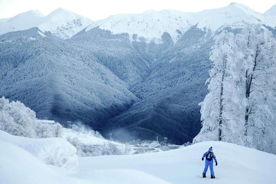 A volunteer rides his snowboard along the practice slope for the alpine ski course of the 2014 Winter Olympics, Saturday, Feb. 1, 2014, in Krasnaya Polyana, Russia. (AP Photo/Jae C. Hong) Photo: Jae C. Hong, Associated Press / AP