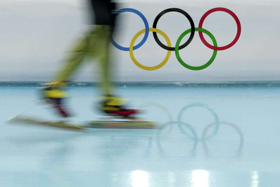 A Japanese skater is blurred by the use of a slow shutter speed on the camera as he passes the Olympic Rings during a warmup lap at Adler Arena Skating Center at the 2014 Winter Olympics, Monday, Feb. 3, 2014, in Sochi, Russia. (AP Photo/Peter Dejong) Photo: Peter Dejong, Associated Press / AP