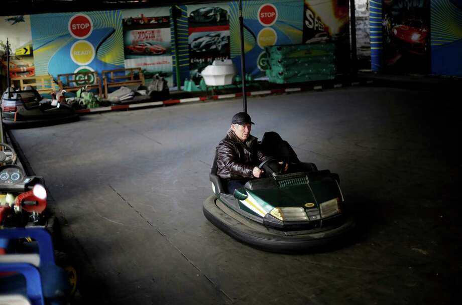 Leonid Semonischev starts up a bumper car as a child's amusement park prepares to open for the day in the Khosta district, Saturday, Feb. 1, 2014, in Sochi, Russia, home of the upcoming 2014 Winter Olympics. (AP Photo/David Goldman) Photo: David Goldman, Associated Press / AP