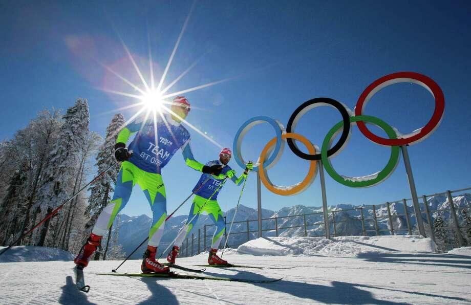 Members of the Slovenian Cross-country ski team ski in front of Olympic rings at Laura Cross-country Ski & Biathlon Center of the 2014 Winter Olympics, Sunday, Feb. 2, 2014, in Krasnaya Polyana, Russia. (AP Photo/Gero Breloer) Photo: Gero Breloer, Associated Press / AP