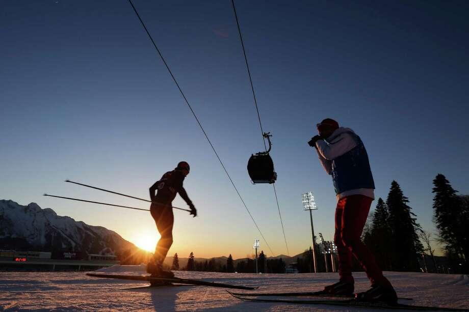 Norwegian biathlete Vetle Sjaastad Christiansen, left, trains as his coach records him at Laura Cross-country Ski & Biathlon Center ahead of the 2014 Winter Olympics, Monday, Feb. 3, 2014, in Krasnaya Polyana, Russia. (AP Photo/Felipe Dana) Photo: Felipe Dana, Associated Press / AP