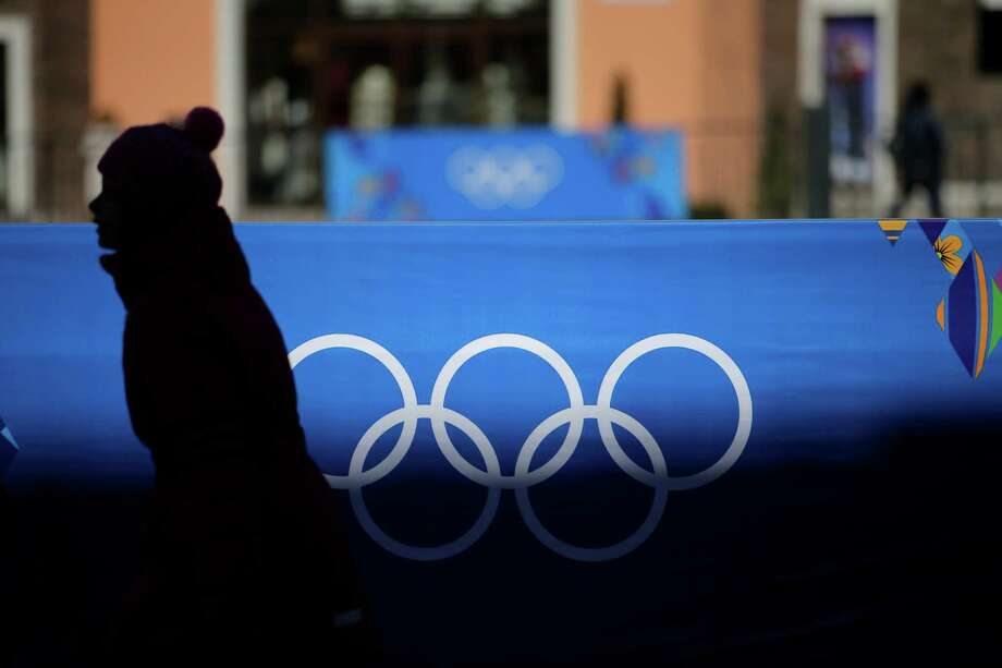 A girl walks past a banner showing the Olympic rings on Monday, Feb. 3, 2014, in Krasnaya Polyana, Russia, as preparations for the 2014 Winter Olympics continue. (AP Photo/Jae C. Hong) Photo: Jae C. Hong, Associated Press / AP