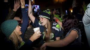 Fans celebrate at Fuel bar Pioneer Square after the Seattle Seahawks 43-8 win agains the Denver Broncos in Super Bowl XLVIII on Sunday, February 2, 2014 in Seattle. (Photo By By CHRIS WILSON/SPECIAL TO SEATTLEPI.COM)
