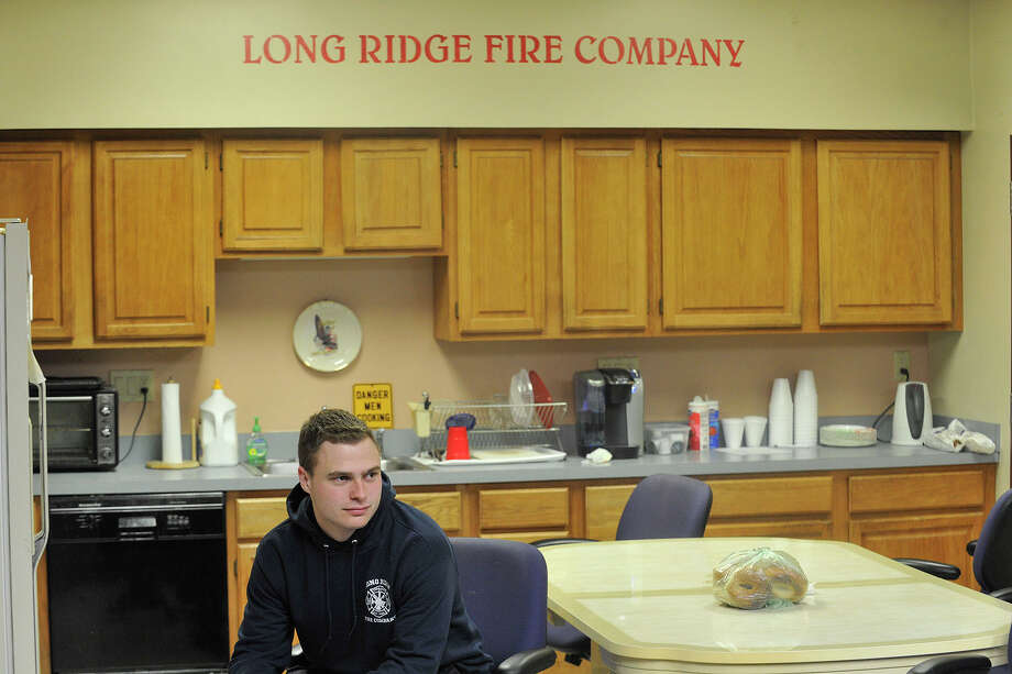 Volunteer firefighter Jake Czelada watches television from the kitchen at the Long Ridge Fire Company in Stamford, Conn., on Tuesday, Feb. 4, 2014. Czelada lives at the fire station rent-free giving him more opportunities to go out on calls. Photo: Jason Rearick / Stamford Advocate