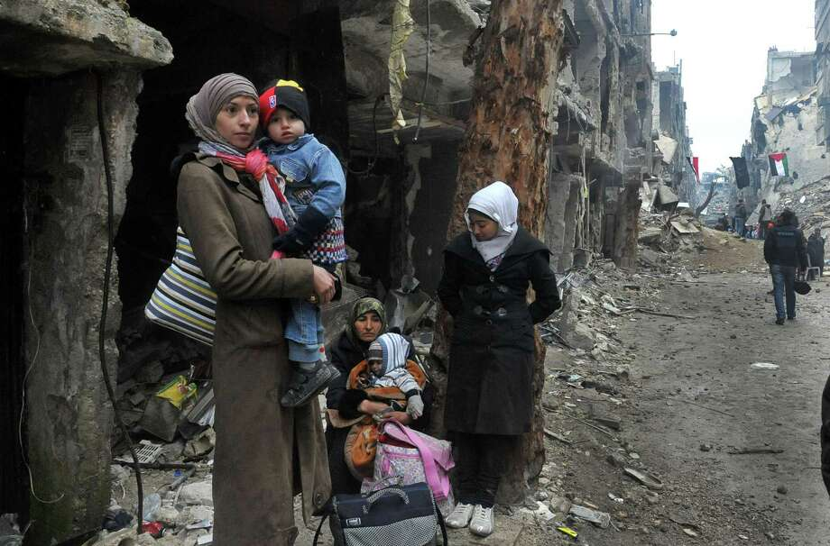 In this photo released by the Syrian official news agency SANA, residents of the besieged Yarmouk Palestinian refugee camp  wait to leave the camp, on the southern edge of the Syrian capital Damascus, Syria, Tuesday, Feb. 4, 2014. Over the past six days the U.N. continued to distribute food parcels in the Palestinian camp where activists say at least 85 people have died as a result of lack of food and medicine since mid-2013. (AP Photo/SANA)  ORG XMIT: BEI108 Photo: Uncredited / SANA