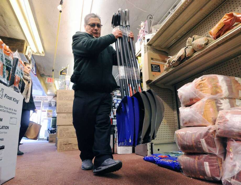 Greenwich Hardware Store employee, Emilio Gomez, stocks snow shovels inside the store in Greenwich, Tuesday afternoon, Feb. 4, 2014. Gomez said the store has had a good winter season selling lots of shovels and winter items such as ice-melt and sleds. The National weather Service is calling for another winter storm early  Wednesday morning that is forecasted to bring snow, sleet and freezing rain to Greenwich with the accumulation of 4-8  inches of snow and ice by the time the storm passes Wednesday night. Photo: Bob Luckey