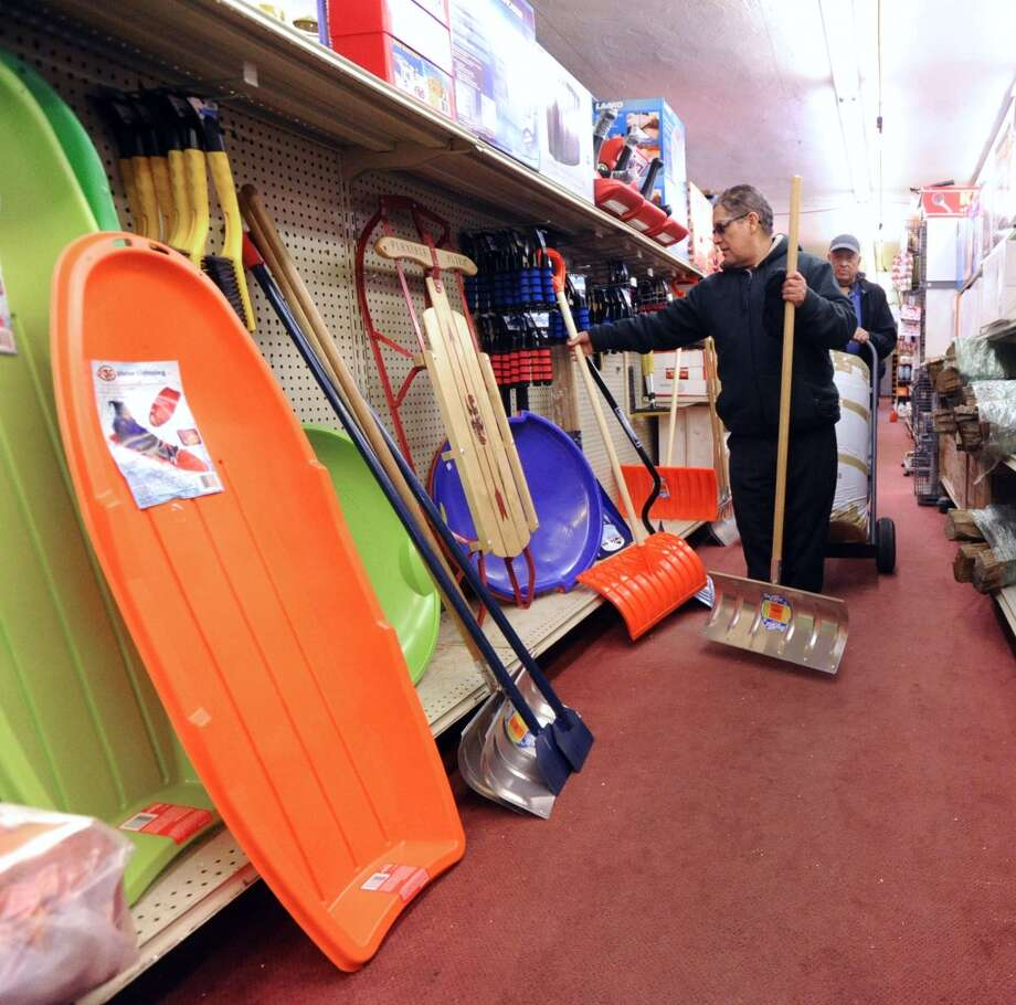 Greenwich Hardware Store employee, Emilio Gomez, stocks snow shovels inside the store in Greenwich, Tuesday afternoon, Feb. 4, 2014. Gomez said the store has had a good winter season selling lots of shovels and winter items such as ice-melt and sleds. The National Weather Service is calling for another winter storm early  Wednesday morning that is forecasted to bring snow, sleet and freezing rain to Greenwich with an accumulation of 4-8  inches of snow and ice by the time the storm passes Wednesday night. Photo: Bob Luckey