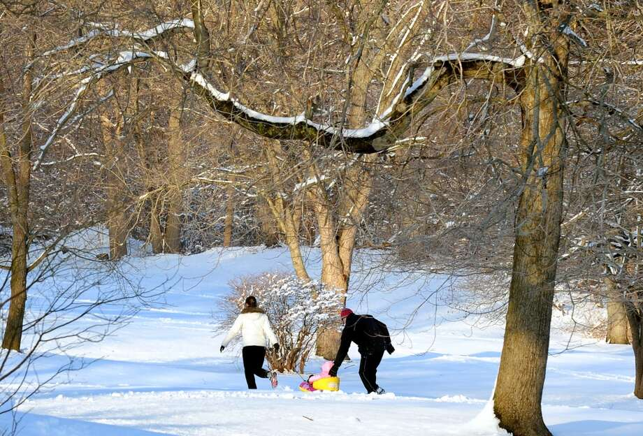 A family walks through the snow at Boothe Memorial Park in Stratford, Conn. on Tuesday February 4, 2014. Photo: Christian Abraham