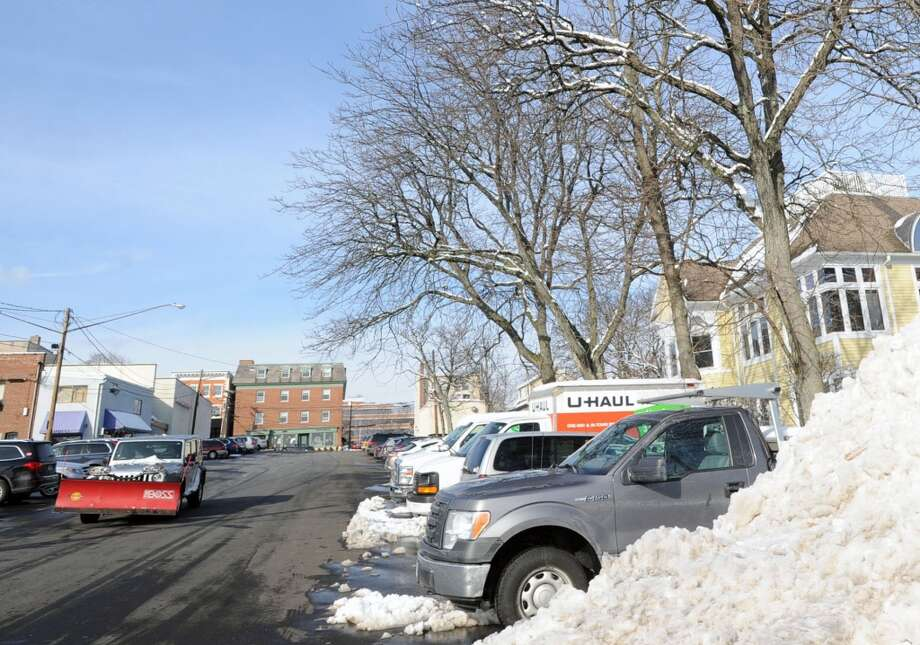 At left, a plow truck passes a plowed snow mound in a central Greenwich praking lot, Tuesday afternoon, Feb. 4, 2014. The National Weather Service is calling for another winter storm early Wednesday morning that is forecasted to bring snow, sleet and freezing rain to Greenwich with an accumulation of 4-8  inches of snow and ice by the time the storm passes Wednesday night. Photo: Bob Luckey