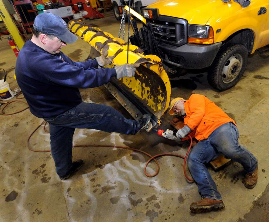 Dan LaMontagne, left, and Don Van DeWater, Bethel Highway Department workers, in Bethel, Conn., change the blade on a snowplow in preparation for Wednesday's snowstorm. Photo: Carol Kaliff