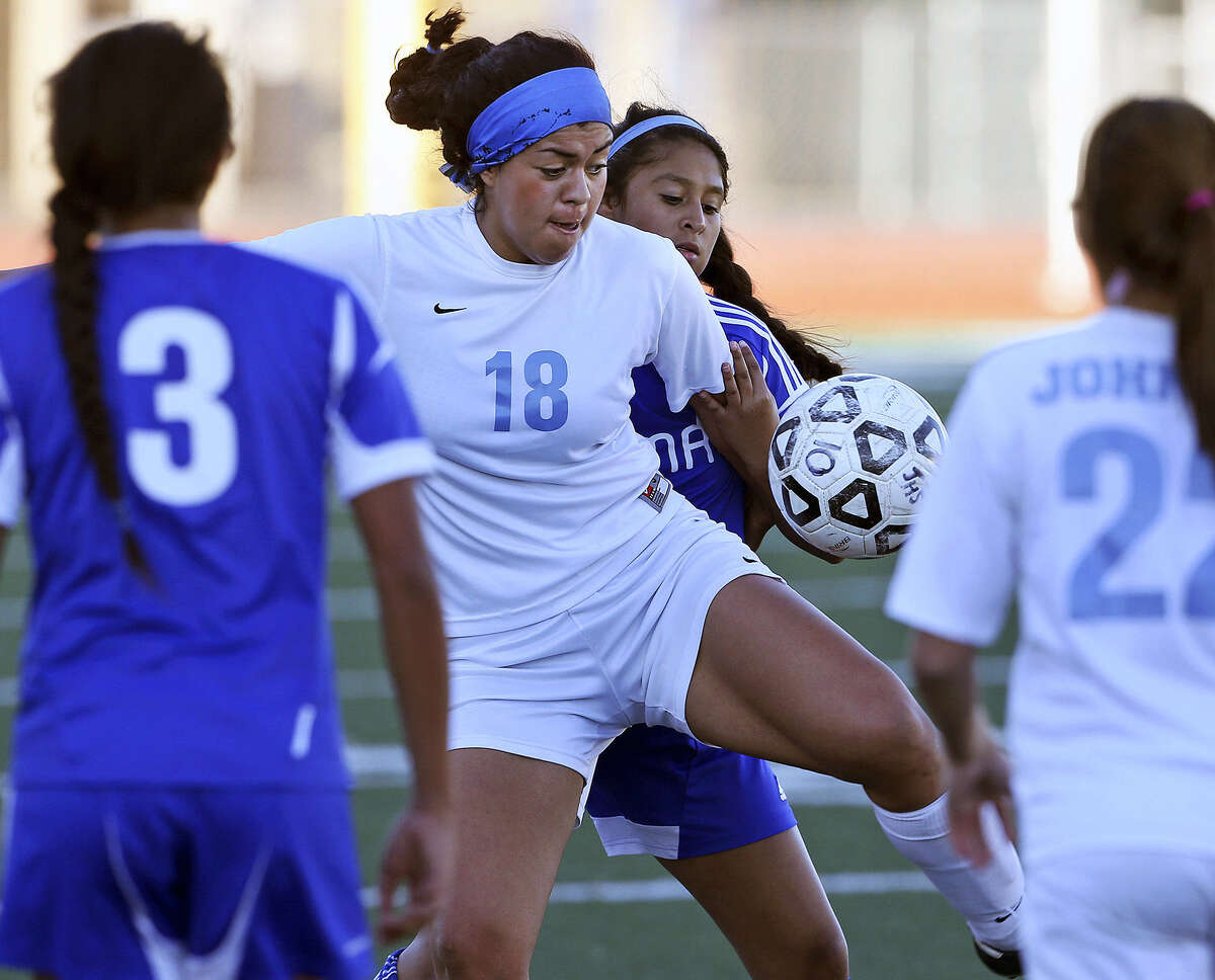 Alexa Ledesma (18) of No. 6 Johnson fights for possession during a 2-1 win over fourth-ranked MacArthur in District 26-5A play Tuesday at Comalander Stadium.
