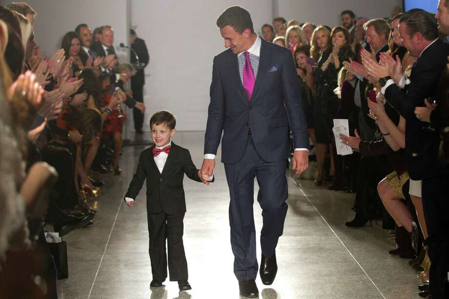 Johnny Manziel walks with 6-year-old Charlie Dina during a charity fashion show Tuesday at Tootsies. Photo: Brett Coomer, Staff / © 2014 Houston Chronicle