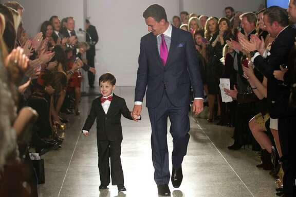 Johnny Manziel walks with 6-year-old Charlie Dina during a charity fashion show Tuesday at Tootsies.
