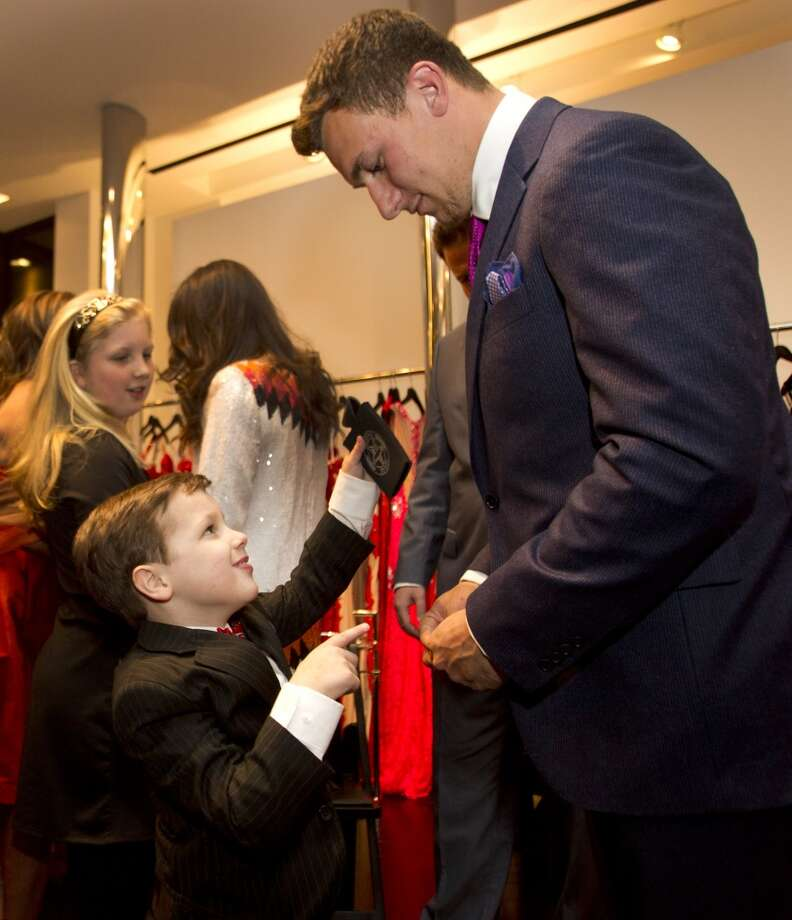 A friendship has blossomed between former Texas A&M quarterback Johnny Manziel and 6-year-old Charlie Dina in recent years as Charlie successfully battled cancer. Photo: Brett Coomer, Houston Chronicle