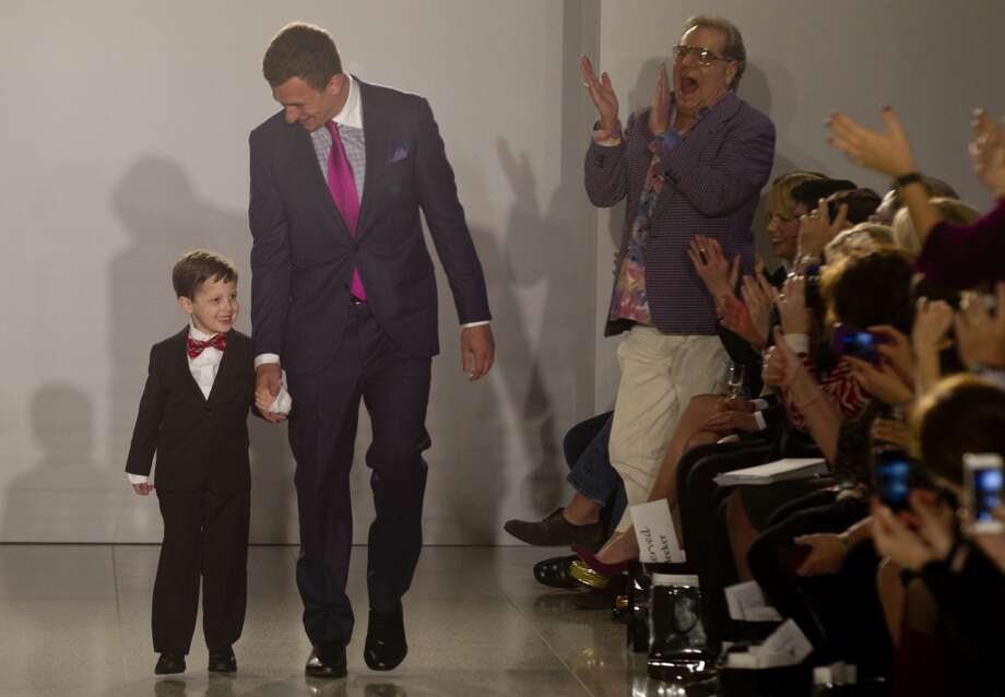 Johnny Manziel walks with 6-year-old Charlie Dina during a charity fashion show Tuesday at Tootsies. Photo: Brett Coomer, Houston Chronicle