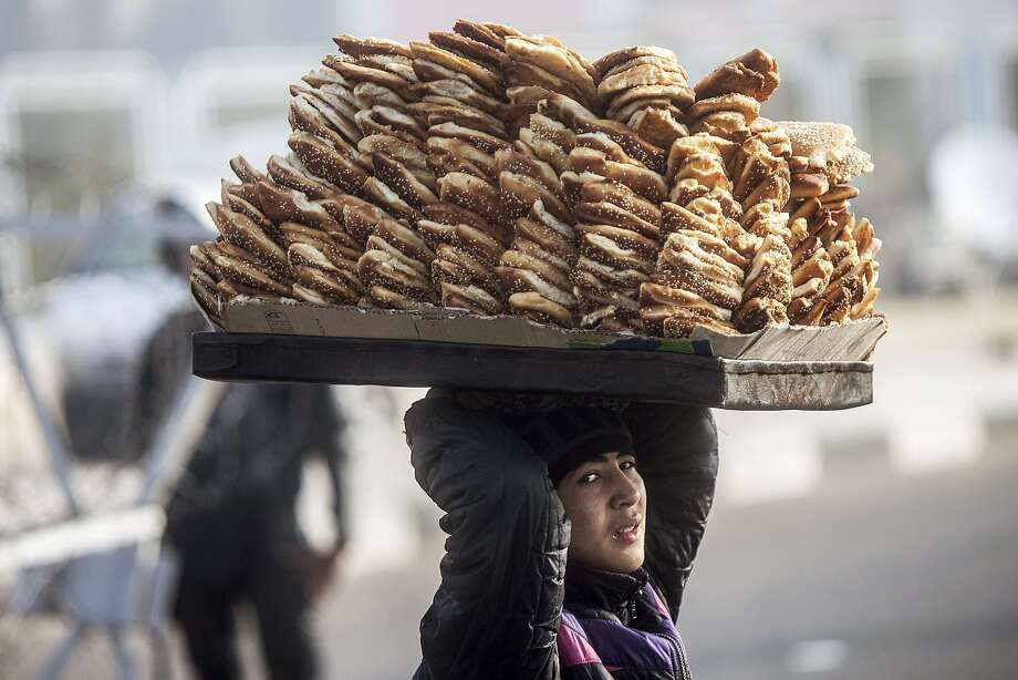 Attention, cadets! Doughnut break! In Cairo, a street vendor carries a towering tray of pastries on his head 