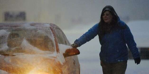Crystal Maylath, 22 of Mechanicville brushes snow from her car after working overnight at the Walmart in Clifton Park. (Skip Dickstein / Times Union)