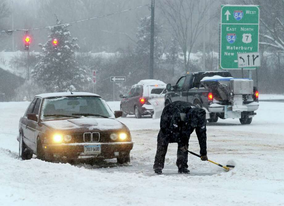 A driver uses a car snow scraper to clear snow from around his car after having difficulty driving up an incline on Mill Plain Road in Danbury, Conn. during a snow storm Wednesday, Feb. 5, 2014. Photo: Carol Kaliff / The News-Times