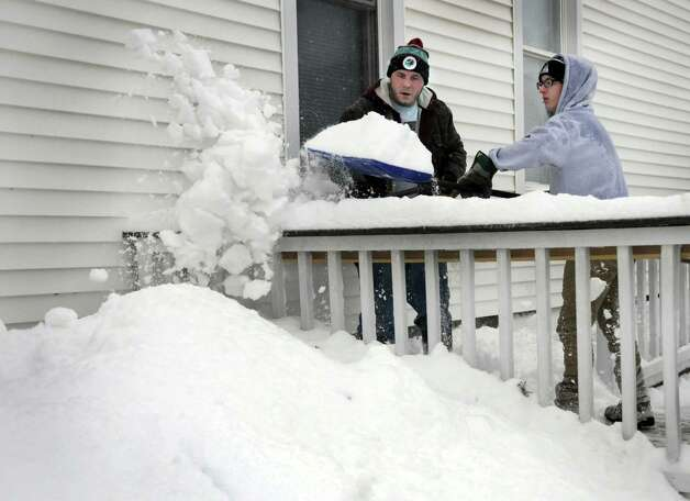 Ben Russell, left, Trevor Skok, 16, shovel snow at a church on Deer Hill Avenue in Danbury, Conn. early Wednesday morning, Feb. 5, 2014, during a snowstorm. Photo: Carol Kaliff / The News-Times