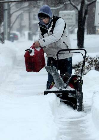 Stefan Skok, 16, refuels the snowblower his is using to clear snow from sidewalks on Deer Hill Avenue in Danbury, Conn. during a snowstorm, Wednesday morning, Feb. 5, 2014. Photo: Carol Kaliff / The News-Times