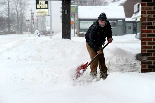 Mike Gagliardi shovels the snow from store fronts on Lake Avenue in Danbury, Conn. early Wednesday, morning Feb. 5, 2014, during a snowstorm. Photo: Carol Kaliff / The News-Times