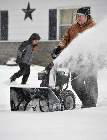 Kevin Simon snowblows his driveway as son Benjamin, 7, enjoys a snow day Wednesday Feb. 5, 2014, in Clifton Park, NY.  (John Carl D'Annibale / Times Union) Photo: John Carl D'Annibale / 00025615A