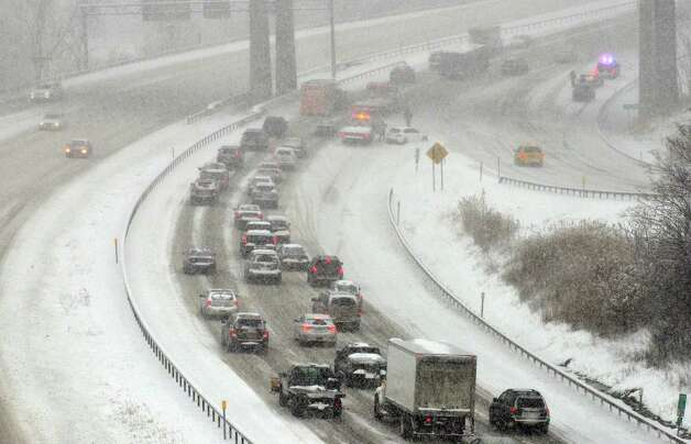 Traffic moves slowly along Interstate 90 in the west bound lanes as emergency personnel clear up car accidents Wednesday morning, Feb. 5, 2014, in Albany, N.Y.  (Paul Buckowski / Times Union) Photo: Paul Buckowski / 00025615A