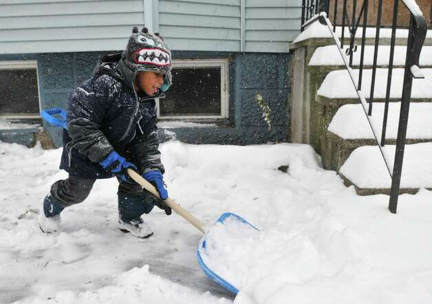 Sahih Brown, 5, of Albany helps his dad out by shoveling their Orange St. sidewalk Wednesday morning, Feb. 5, 2014, in Albany, N.Y.  (Paul Buckowski / Times Union) Photo: Paul Buckowski / 00025615A