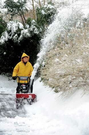 Deuk Chang clears his Mayfair Rd. driveway in Fairfield, Conn. after overnight snowstorm on Wednesday, Feb. 5, 2014. Most towns and cities got at least 7 inches of snow before temperatures rose after dawn and a changeover to sleet and freezing rain began. Photo: Cathy Zuraw / Connecticut Post