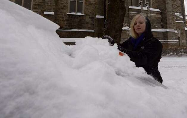 Ashley Dzingle 24, of Albany removes snow from her car on Wednesday. (Skip Dickstein / Times Union)