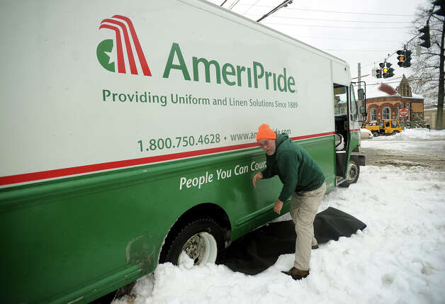 Delivery driver Tim Schmidt lays a carpet in front of his truck's rear tires to try to gain some traction after becoming stuck in the snow at the intersection of Broad and River Streets in downtown Milford, Conn. on Wednesday, February 5, 2014. Photo: Brian A. Pounds / Connecticut Post