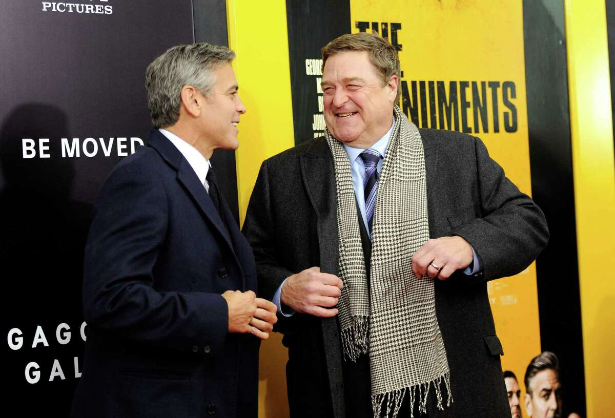 """Actors George Clooney, left, and John Goodman attend the premiere of """"The Monuments Men"""" at the Ziegfeld Theatre on Tuesday, Feb. 4, 2014, in New York. (Photo by Evan Agostini/Invision/AP) ORG XMIT: NYEA101"""