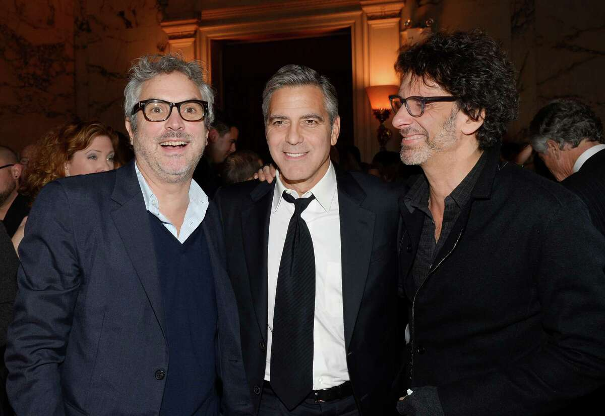 """Directors Alfonso Cuarón, left, George Clooney and Joel Coen attend """"The Monuments Men"""" premiere party at the Metropolitan Club on Tuesday, Feb. 4, 2014 in New York. (Photo by Evan Agostini/Invision/AP) ORG XMIT: NYEA137"""