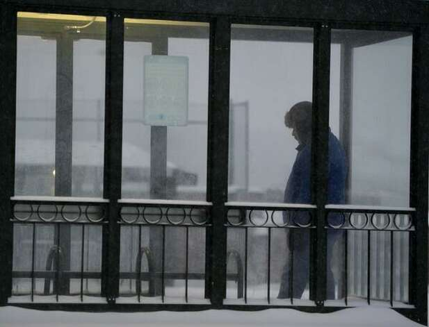 A commuter uses a bus stop as refuge from the snow in Colonie on Wednesday. (Skip Dickstein / Times Union)