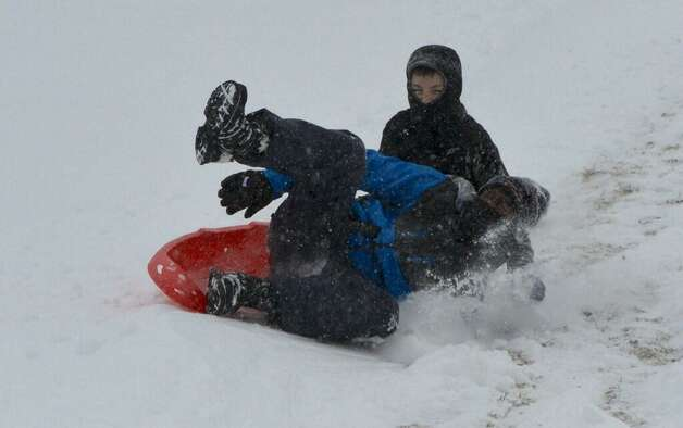 Rickie Massie, 15, foreground and Ethan Holt, 11, have a rough go of their sledding on the hill near Albany Academy. (Skip Dickstein/Times Union)