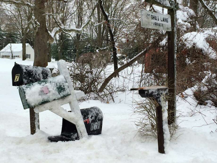 These three mailboxes on Greens Farms Road, near the entrance to a private road, were damaged by wet snow thrown by a passing plow. The box sitting on the snow was knocked off its post. Resident Steven Shore, who took this picture, said he counted 25 damaged or destroyed mailboxes in the neighborhood. Photo: Contributed Photo / Westport News