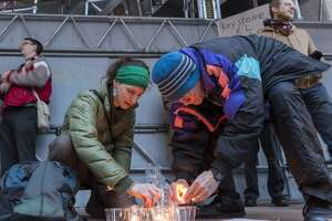 Environmental activists gather at the Mickey Leland Federal Building in downtown Houston for a candlelight vigil urging President Obama to reject the Keystone XL pipeline. Stephanie Thomas (left) and Jim Williams struggle against the breeze to light the candles for the vigil.